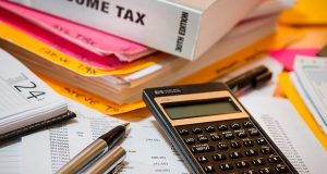 Income tax papers and calculator on desk